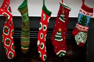 5 Christmas stockings hung on fireplace mantle